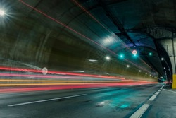 Red and orange trails of car lights passing fast through the highway tunnel in perspective.
