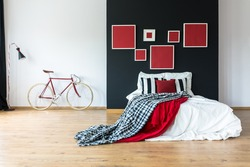 Red and patterned coverlet on king-size bed against black wall with paintings in bedroom with bike