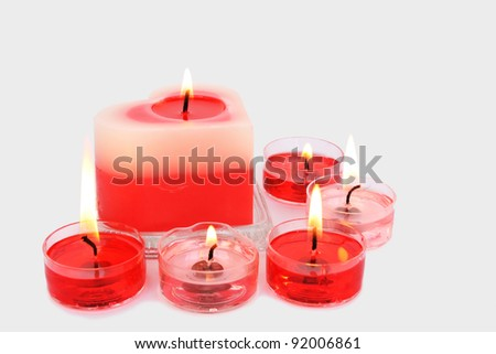 Red and pink candles isolated on grey background.