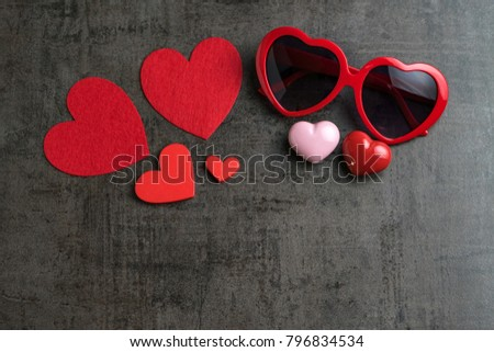 Red and pink heart shapes with heart shape eyeglasses on black cement wallpaper as Valentine's day concept with copy space. #796834534