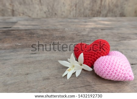 Red and pink knitting hearts with Millingonia on the wooden rough table. Background of the rock wall. Sun light shines on the frame. Copy space for editing and text. #1432192730