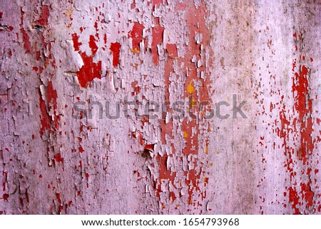 Red and pink paint chip worn metal texture. old chipped and burned out paint on an iron wall. Corrosion of metal. a lot of peeling paint
