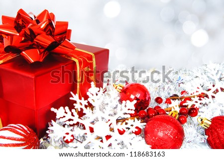 Red and silver Christmas scene with gift box, baubles and abstract light background