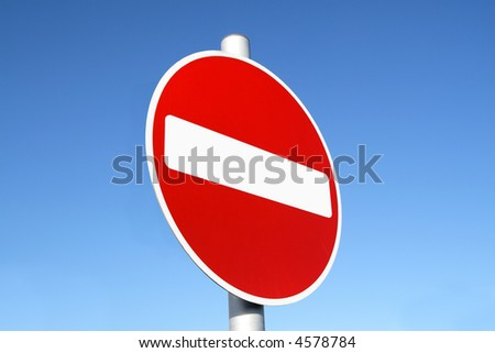Red and white british no entry road sign with a blue sky.