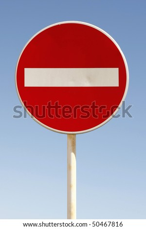 Red and white british no entry road sign with a blue sky