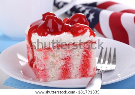 Red and white cake on a white plate with blue napkins and American flag in background - stock photo