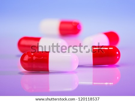 Red and white capsules (bolus) on violet, macro view medical concept - stock photo