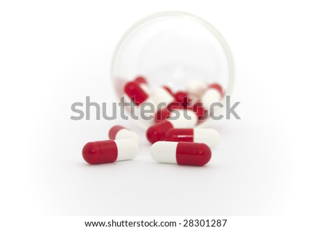 red and white capsules spilling out of bottle