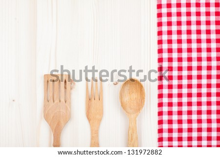 Red and white checkered tablecloth, fork, spoon on white wood background