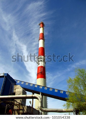 red and white chimney against a blue sky and green tree