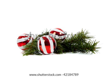 Red and white Christmas balls/baubles with a pine tree branch on a white background