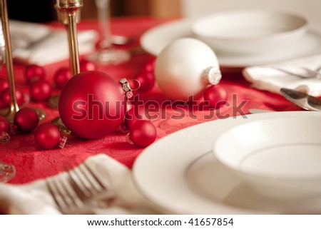 Red and white Christmas table setting, shallow depth of field, focus on ornament