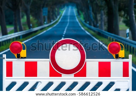 Red and white colored street barrier on empty road at night/Closed Road at Darkness