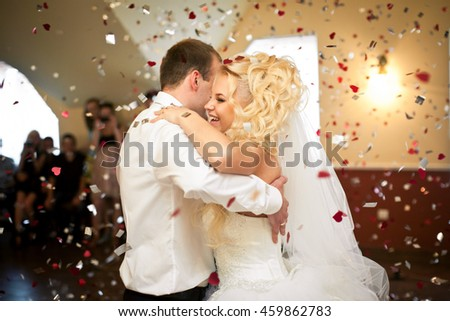 Red and white confetti falls around dancing wedding couple
