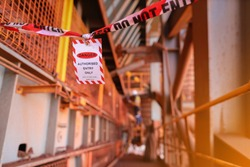 Red and white danger tag  exclusion zone tape with sign barricade working area off as dropped object zone high risk work with defocused worker background construction site, Perth city Australia