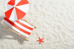 Red and white deckchair on the beach: top view