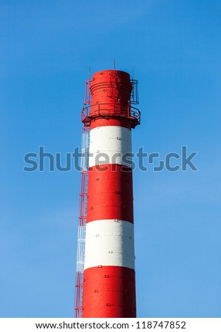 Red and white factory chimney against blue sky