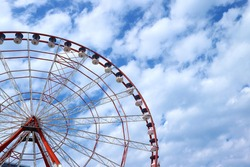 Red and White Ferris Wheel Against Blue and Cloudy Sky with Copy Space