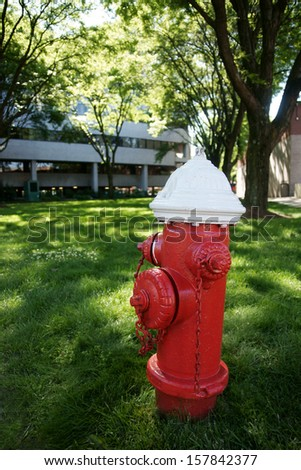 Red and white fire hydrant on a grassy lawn in front of office buildings