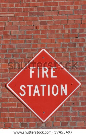 Red and white fire station sign on the outside of a brick fire station