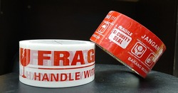 Red and White Fragile and Fragile Tape In Front Of The Black Background