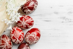 Red and white handmade Easter eggs. Ukrainian pysanka decorated with wax-resist dyeing technique. White wooden background with copy space for text