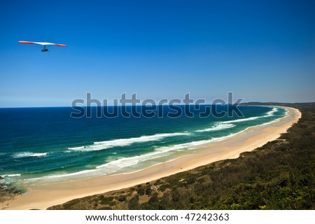 Red and White Hang Glider Flying High Over Beach at Byron Bay in New South Wales