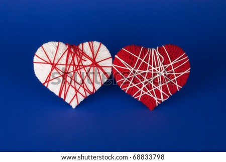 Red and white heart of woolen yarn on a blue background. Valentine's Day