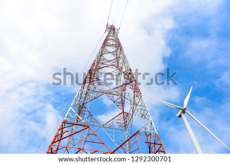 red and white high voltage post,High voltage tower and wind turbine for electric production on blue sky background #1292300701