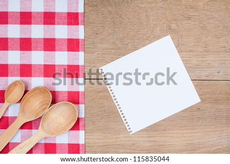 Red and white kitchen textile texture, wooden spoons, old note paper on wood textured background