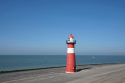 Red and white lighthouse on a blue sky background, Westkapelle in The Netherlands.