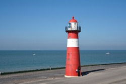 Red and white lighthouse on a blue sky background, Westkapelle, The Netherlands