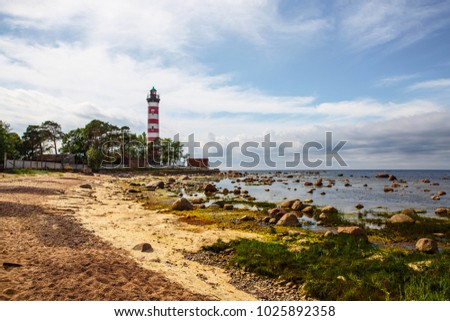 Red and white lighthouse. Rocky seashore #1025892358