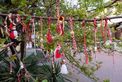 Red and white Martenitsa or Martisor bracelets, hanging on the branches of the blooming tree - Bulgarian and Romanian spring tradition