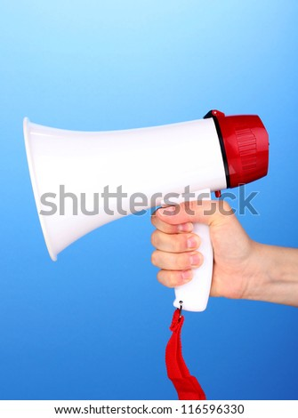 red and white megaphone in hand on blue background