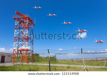 Red and white metal radar tower in airport area with multiple exposure landing plane