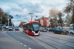Red and white modern tram on the street in Perm, Russia. New trams for Russian cities.