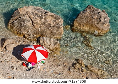 Red and White Parasol on the Rocky Beach in Croatia