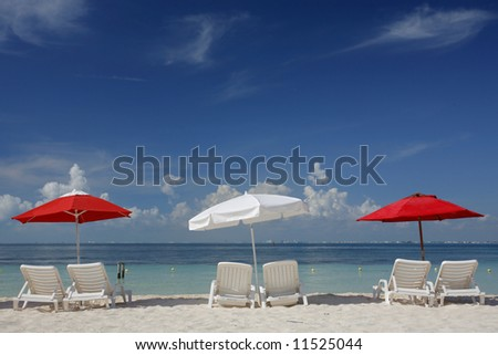 Red and white parasols on a tropical beach with nice blue sky