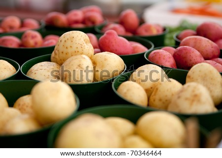 Red and white potatoes in containers at a farmers market.