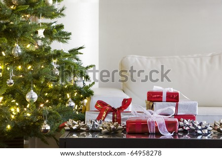 red and white presents by christmas tree in modern living room