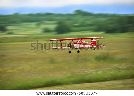 Red and white radio controlled aircraft with methanol engine flying over grassy field. The image shows motion blur.