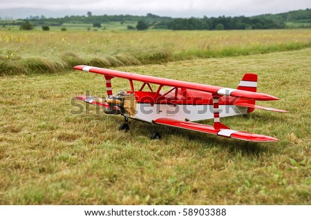 Red and white radio controlled aircraft with methanol engine on a grassy field.