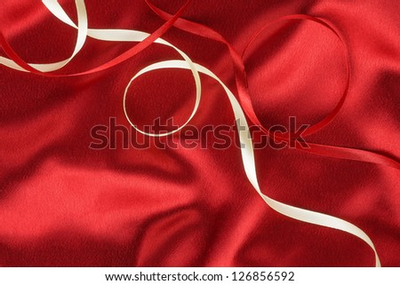 Red and white ribbon on a red silk, as background