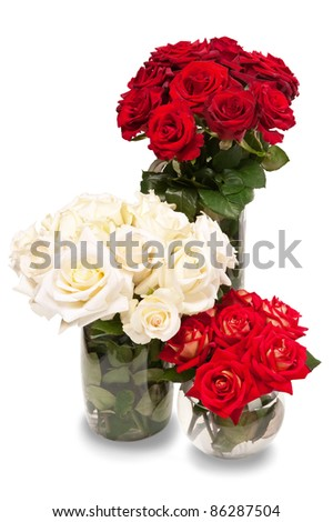 Red and white roses in a vases with water on a white background