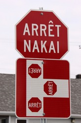 red and white stop sign with stop text in French and local native canadian Innu language (arrêt = stop, nakai = stop)