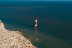 Red and white–striped Beachy Head Lighthouse against chalk cliffs,  view from top of Seven Sisters, Clifftop Paths Nature Reserve. South of England