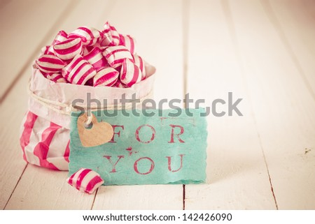 Red and white striped candy in a matching striped paper packet with a blue gift label with the words For You on a background of white wooden boards
