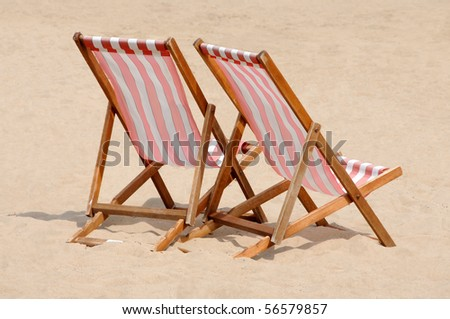Red and white striped deckchairs on a British beach