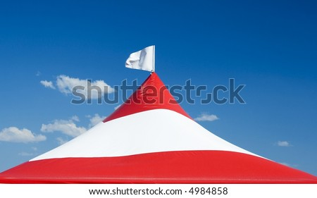 Red and white striped tent with a white flag.